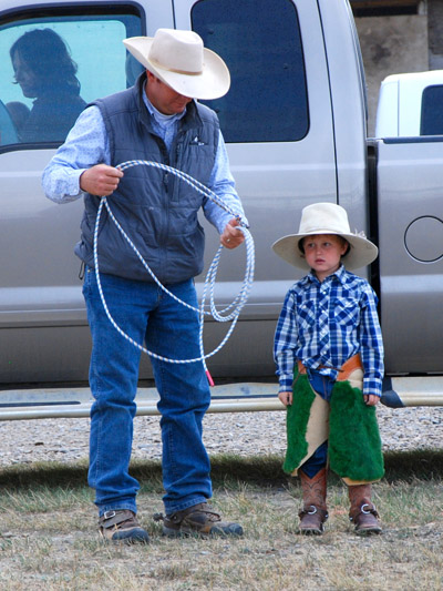 A very young cowboy learning the ropes