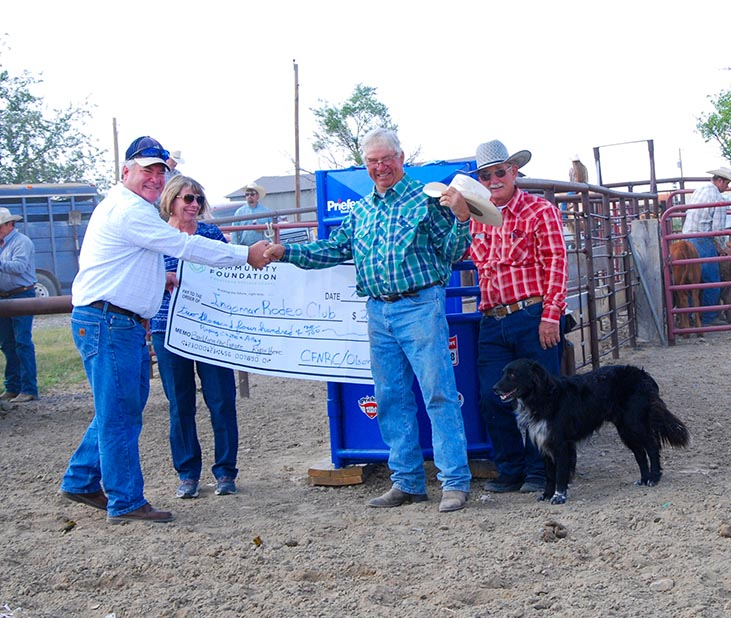 CFNRC (Community Foundation of Northern Rosebud County) President Darrel Grogan and Secretary Stephanie Schwarzkopf present $2400 check to Ingomar Rodeo Club Director Donald John Cameron and President Howard Newman at the Ingomar Open Rodeo.